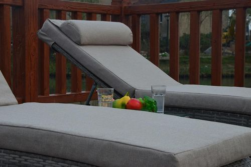 Rustic grey rattan sun loungers and table