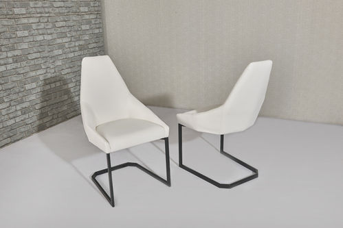 White faux leather dining chairs with shaped backs