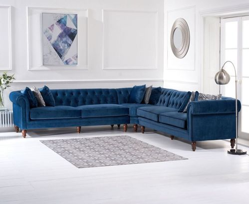 Blue plush velvet corner sofa with cushions