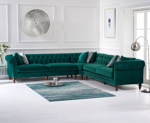 Green plush velvet corner sofa with cushions