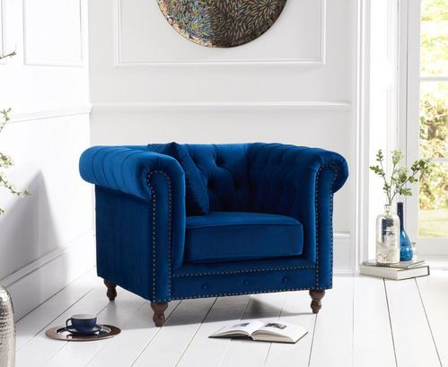 Stylish blue velvet armchair with stud detail