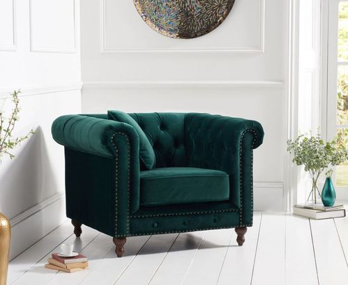 Stylish green velvet armchair with stud detail