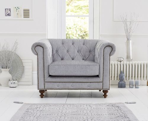 Light grey velvet armchair with stud detail